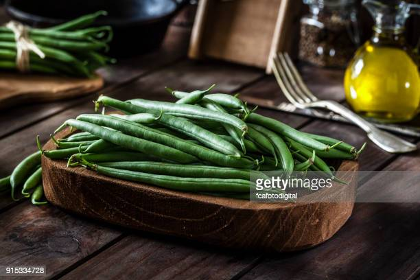 Fresh organic green beans shot on rustic wooden table