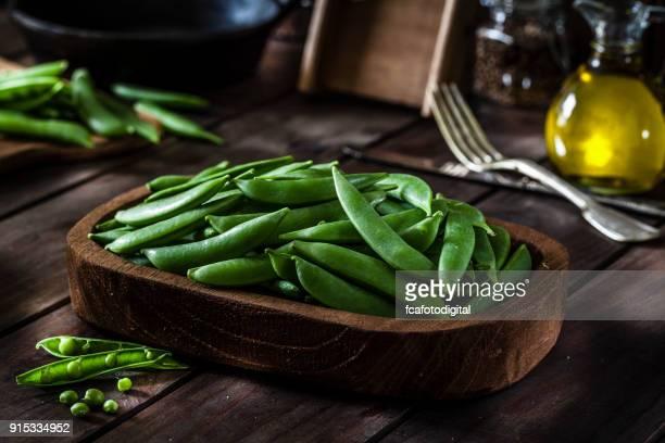 Frische Bio grüne Erbsen auf rustikalen Holztisch erschossen