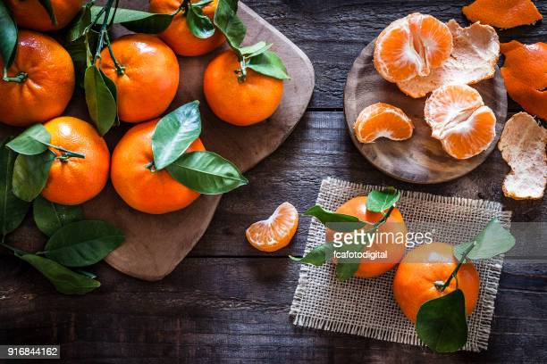 fresh organic mandarins on rustic wooden table - orange imagens e fotografias de stock