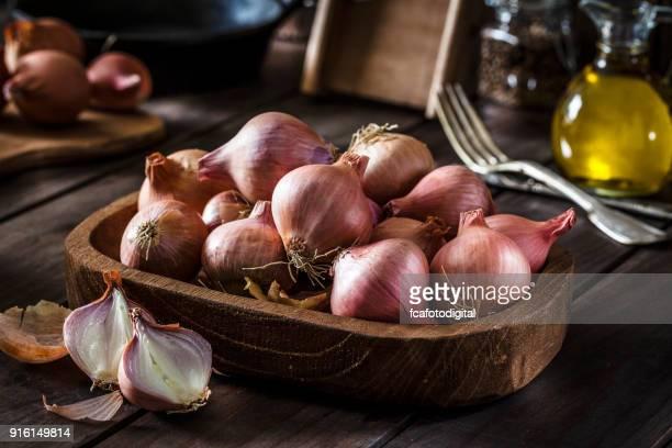Cebollas orgánicas frescas en mesa de madera rústica