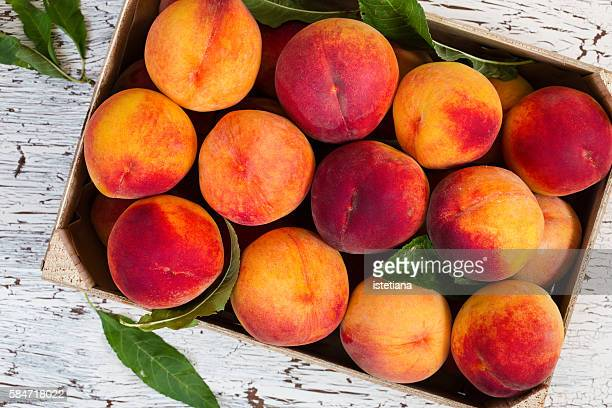 Fresh organic peaches in wooden crate viewed from above
