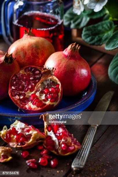 Frescas orgánicas granadas en mesa de madera rústica