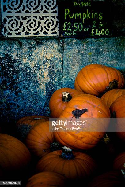 fresh organic pumpkins against wall with price tag at market - malton stock pictures, royalty-free photos & images