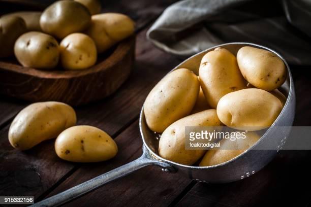 Patatas crudas orgánicas frescas en un colador de metal viejo