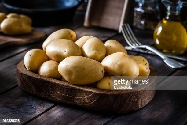 Patatas crudas orgánicas frescas en mesa de madera rústica