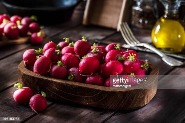 Rábano rojo orgánico fresco en mesa de madera rústica