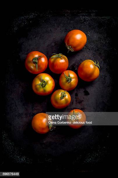 Fresh organic red tomatoes on a dark surface