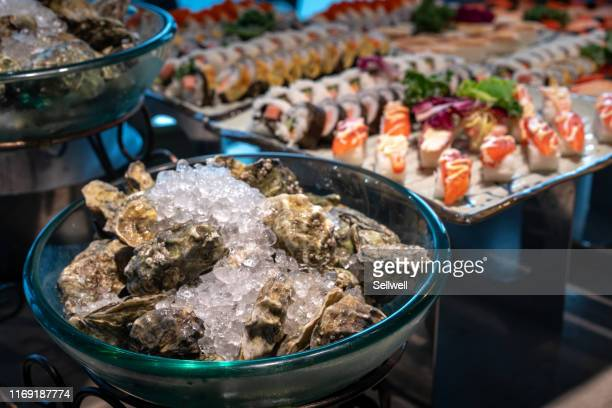 fresh oysters and sushi on the table - raw food diet stock pictures, royalty-free photos & images