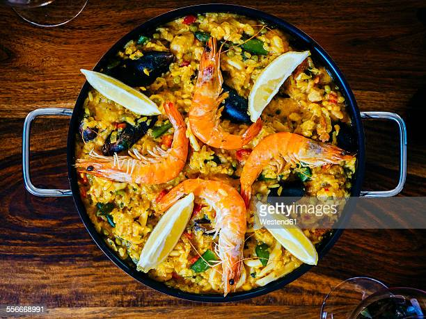 fresh paella in pan on wooden table - paella stock photos and pictures