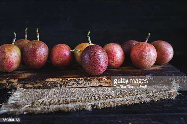 Fresh Passion Fruits On Cutting Board And Jute Against Black Background