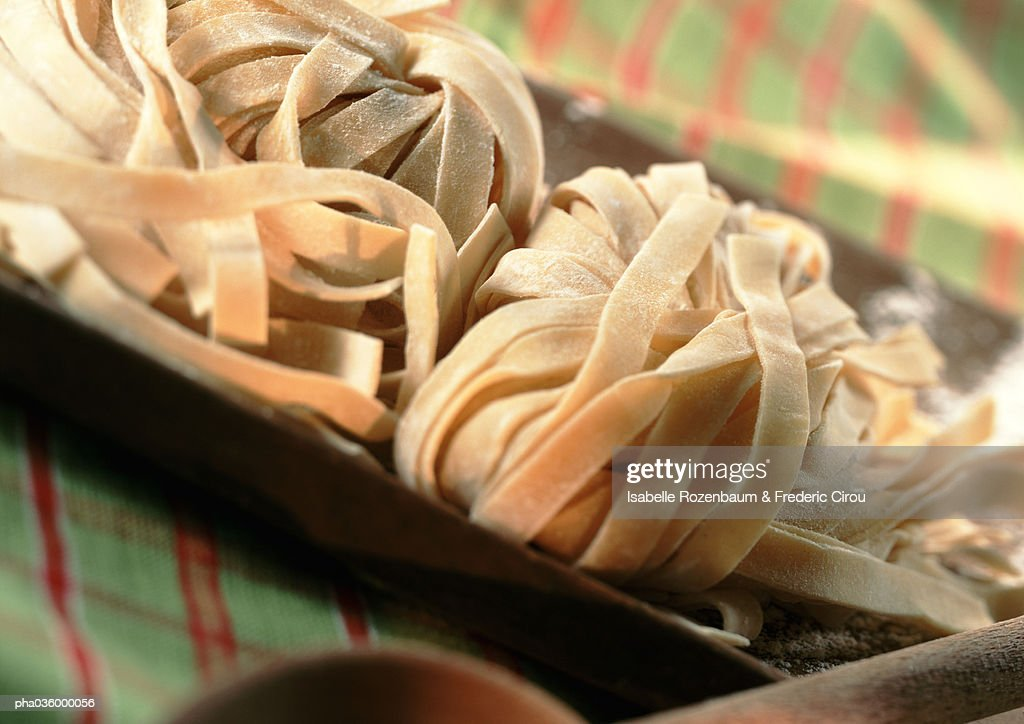 Fresh pasta in dish on green and red tablecloth, close-up : Stockfoto