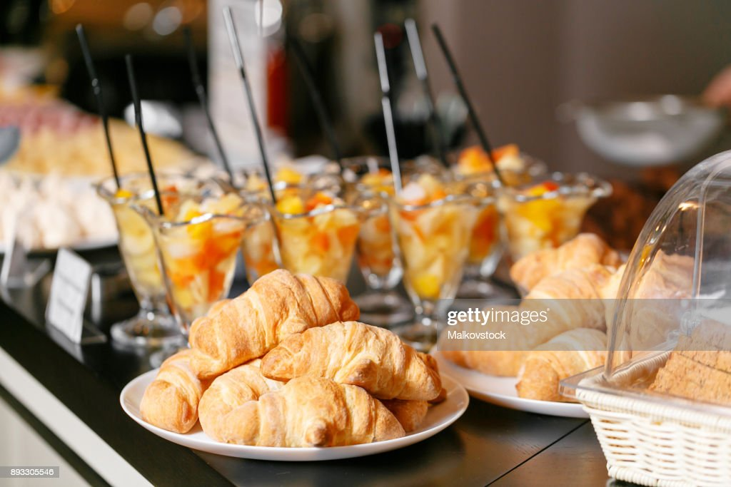 Fresh pastry, crispy morning croissants, hotel breakfast buffet. Dessert fruit cocktail in cups : Foto de stock