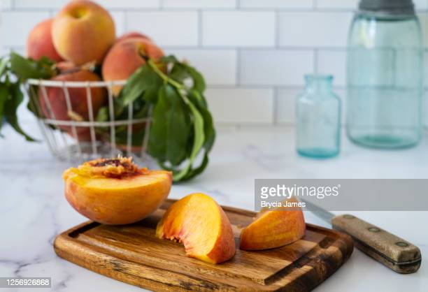 fresh peach cut on a cutting board - brycia james stock pictures, royalty-free photos & images