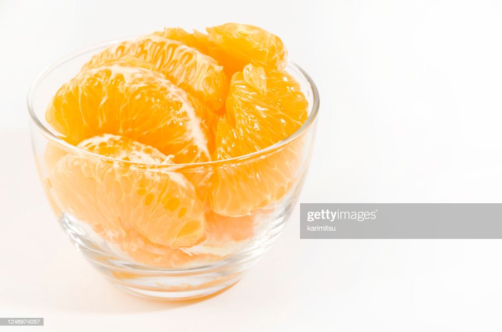 Fresh peeled Hassaku Orange in Transparent Glass bowl on white background : Stock Photo