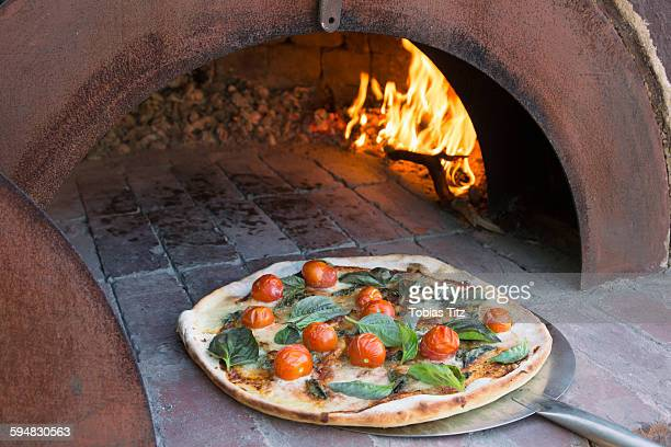 Fresh pizza on peel in traditional oven