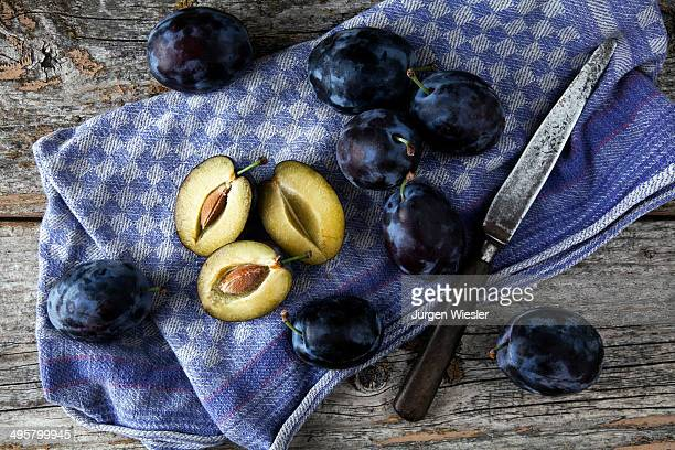 Fresh plums -Prunus domestica- on a kitchen towel, with a knife