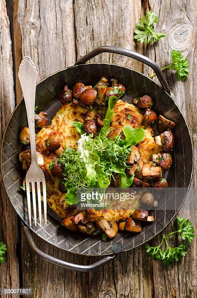 Fresh potato rosti in a pan with mushrooms and salad