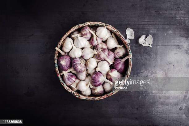 fresh purple garlic in  basket made from newsprint papers - garlic stock pictures, royalty-free photos & images
