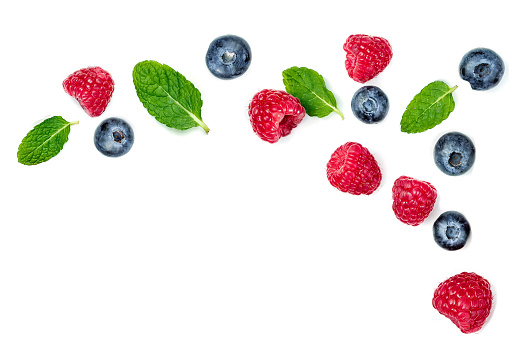 Fresh  raspberries and blueberries with leaves isolated on white background. Berry ornament 945808942