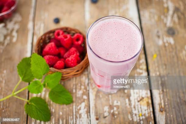 Fresh raspberry milkshake in glass, raspberries