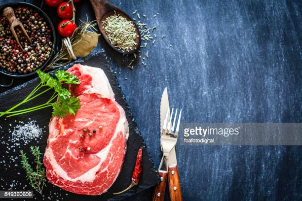 fresh raw beef steak on dark background - red meat stock pictures, royalty-free photos & images