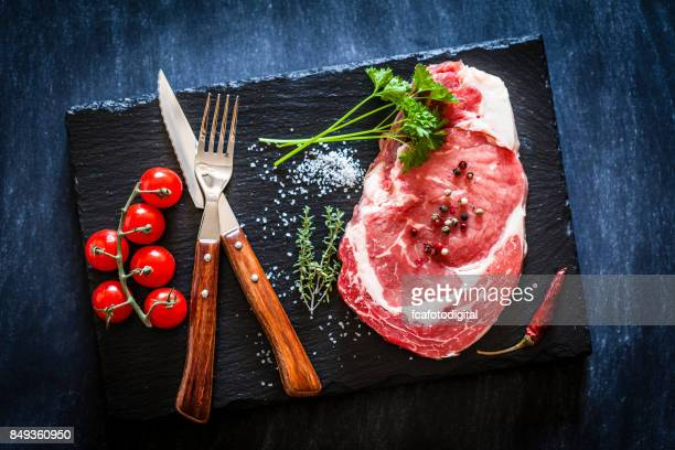 Fresh raw beef steak on dark slate background