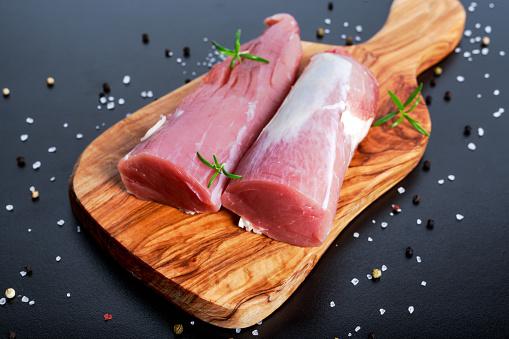Fresh Raw pork tenderloin on wooden board .ready to cook 531535100