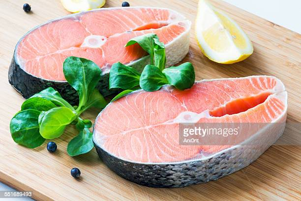 fresh raw salmon steaks on wooden board - fresh seafood stock photos and pictures