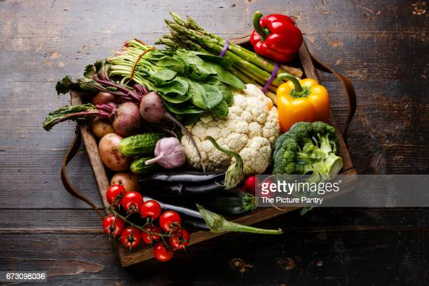 Fresh raw vegetables in wooden box on wooden background