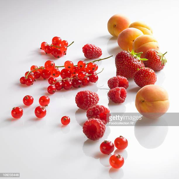 Fresh red berries and apricots on white background, close-up