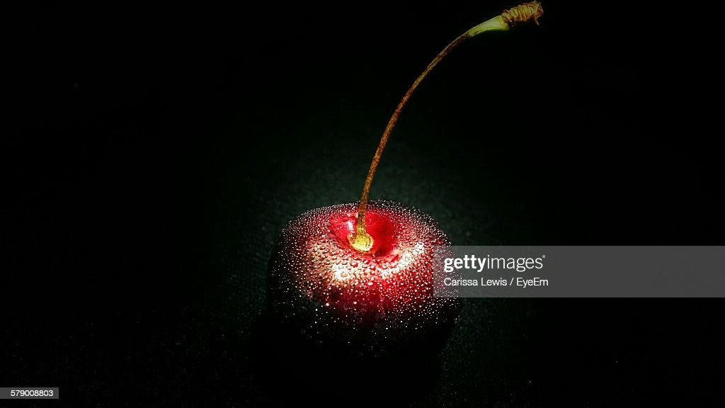 fresh red cherry with water drops against black background ストック