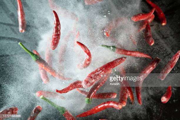 fresh red chili dancing in mid air captrued with high speed sync. - red chili pepper stock pictures, royalty-free photos & images