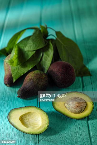 Fresh ripe avocado cut in half next to a cutting knife, on an old wooden turquoise coloured table, with avocados and avocado leaves in the background.