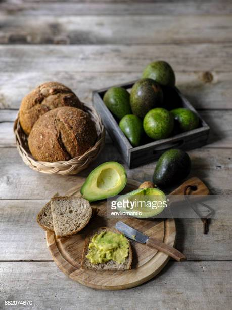 Fresh ripe avocado cut in half with fresh flesh spread onto wholewheat organic brown bread, on a wooden cutting board on an old wooden table, with a bowl of ripe and unripe avocados and bread in a basket in the background.