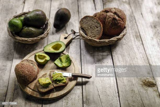 fresh ripe avocado cut in half with fresh flesh spread onto wholewheat organic brown bread, on a wooden cutting board on an old wooden table, with a bowl of ripe and unripe avocados and bread in a basket in the background. - unripe stock photos and pictures