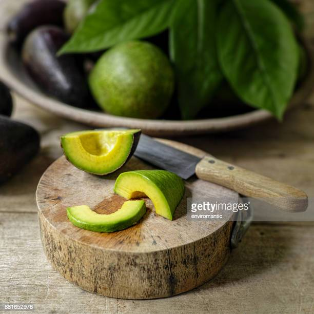 Fresh ripe avocado cut in slices, on a wooden cutting board on an old wooden table, with a bowl of ripe and unripe avocados in the background.