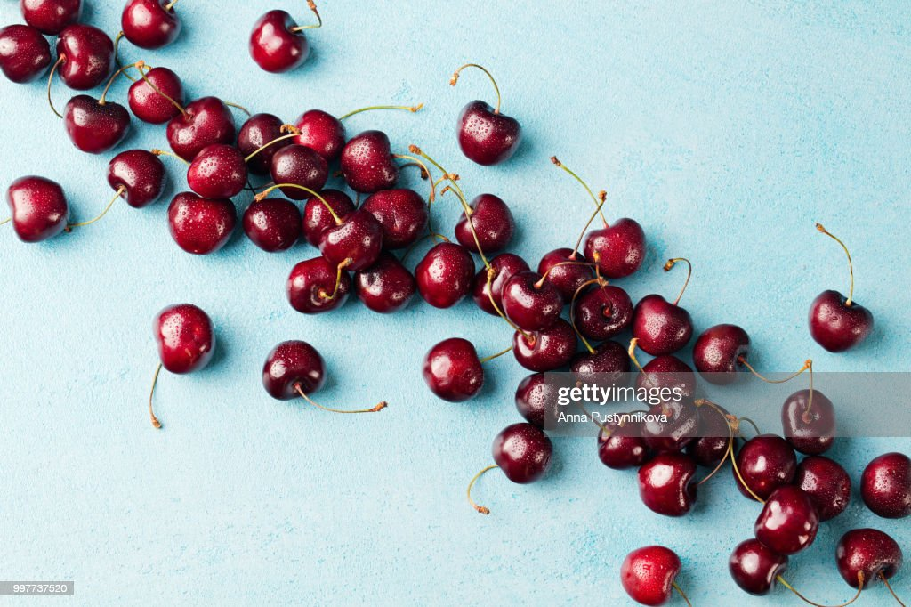 Fresh Ripe Black Cherries On A Blue Stone Background Top View Copy Space Stock Photo