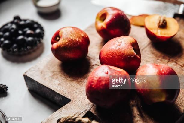 frische reife nektarinen auf einem holzschneidebrett - körperbewusstsein stock-fotos und bilder