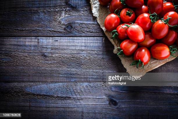 fresh ripe tomatoes on crumpled brown paper still life - tomato stock pictures, royalty-free photos & images