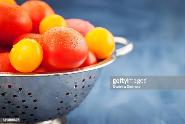 Fresh ripe wet red and yellow tomatoes in colander