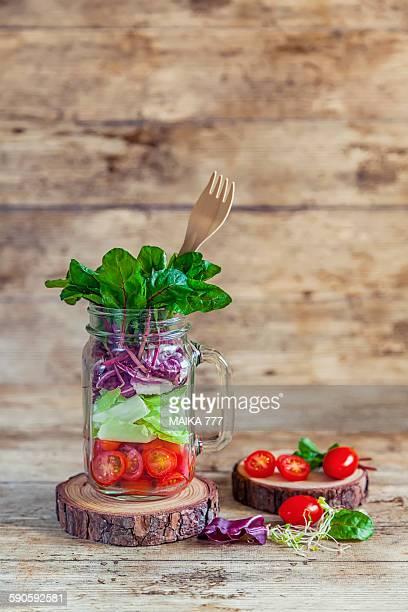 Fresh salad in a mason jar on wooden background