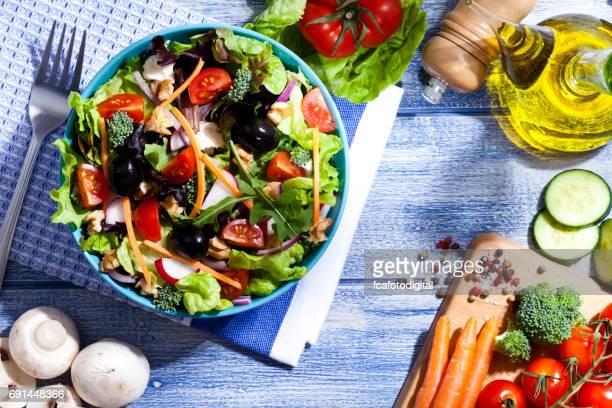 Placa de ensalada en la mesa de picnic azul