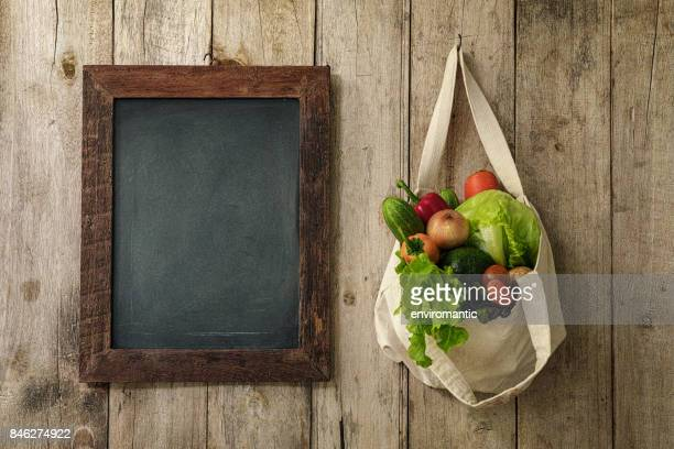 Verduras de ensalada fresca en una bolsa reutilizable de algodón natural colgado junto a una pizarra en blanco enmarcada madera de una vieja pared de tablón de madera.