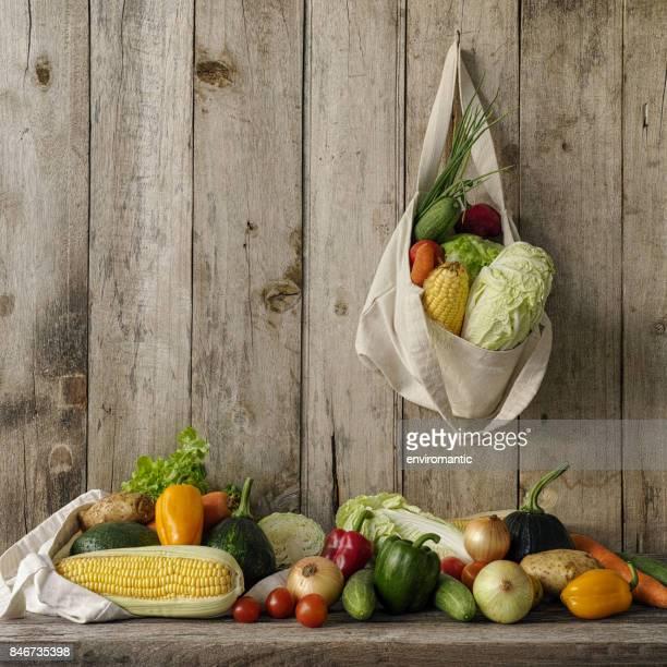 古い木の板壁に掛かっている自然綿の再利用可能な袋に新鮮なサラダ野菜。