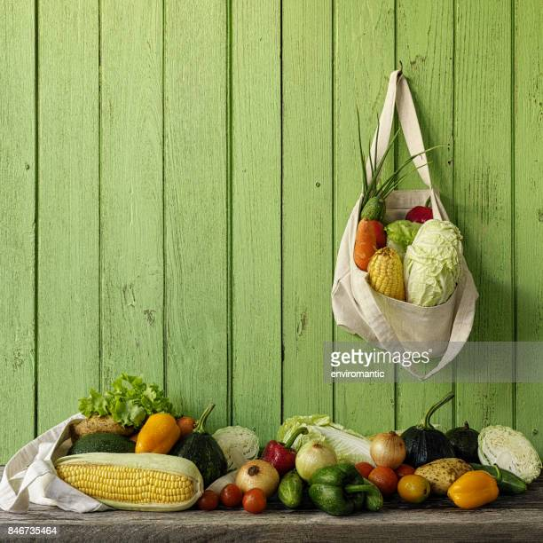 Fresh salad vegetables in a natural cotton reusable bag hanging on an old green wooden plank wall.