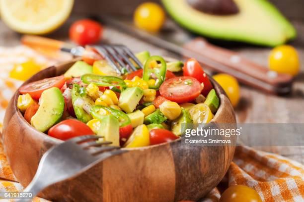 Fresh salad with avocado, corn and tomato.