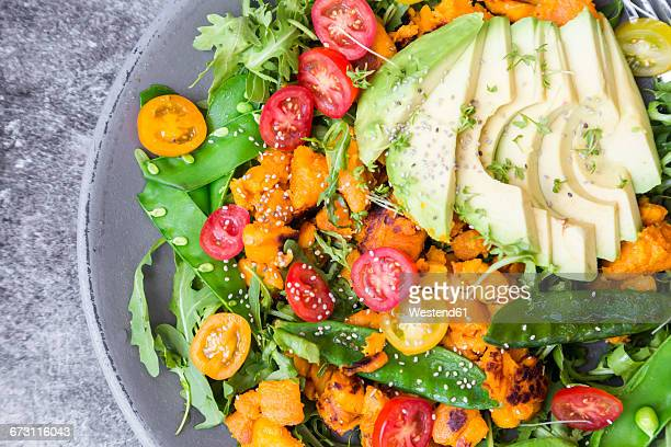 Fresh salad with rocket, sweet potato, avocado, tomato, chia seeds, sugar shots