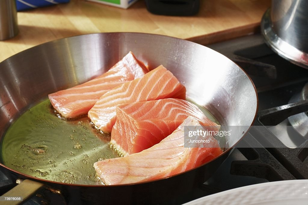 Fresh salmon frying in a pan : Stock Photo