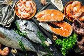 Fresh salmon steak with a variety of seafood and herbs.