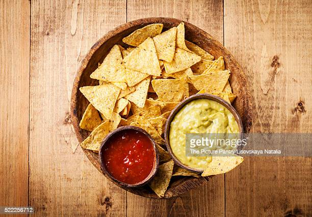Fresh salsa and guacamole dips with nachos chips on wooden backg